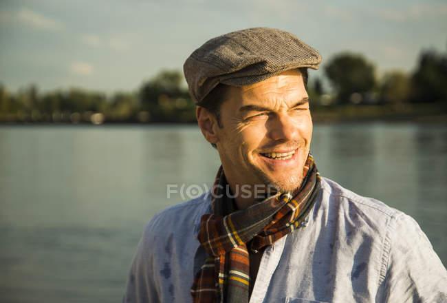 Retrato de homem sorridente, vestindo boné em pé na frente de um rio no crepúsculo da noite — Fotografia de Stock