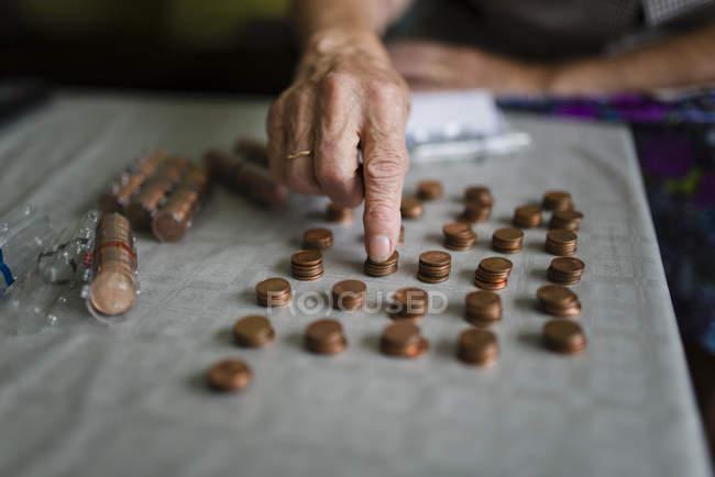 Старуха считает деньги, делает пачки евро центов — стоковое фото