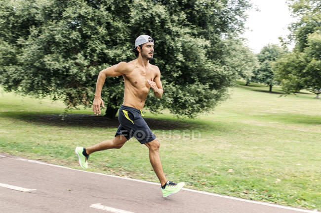 Athletic young man jogging in the park — Stock Photo