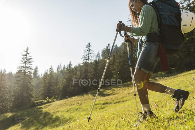Austria, Tyrol, Tannheimer Tal, young woman hiking on alpine meadow — Stock Photo