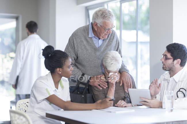 Crying senior woman with husband at clinic talking to doctor and nurse — Stock Photo