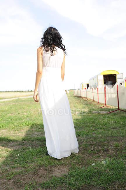 Темноволосый молодой женщине носить белое платье стоя на лугу — стоковое фото