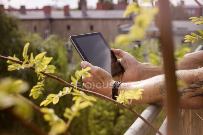Alemanha, Berlim, Homem segurando tablet digital na varanda — Fotografia de Stock