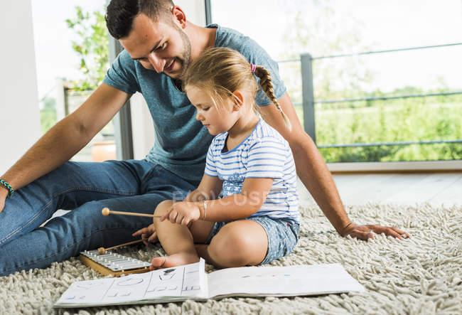 Padre con figlia sul tappeto che suona lo strumento musicale — Foto stock