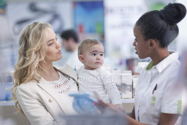 Pharmacist assisting client with baby in drugstore — Stock Photo