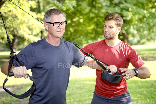 Man doing TRX training while his personal trainer watching him — Stock Photo