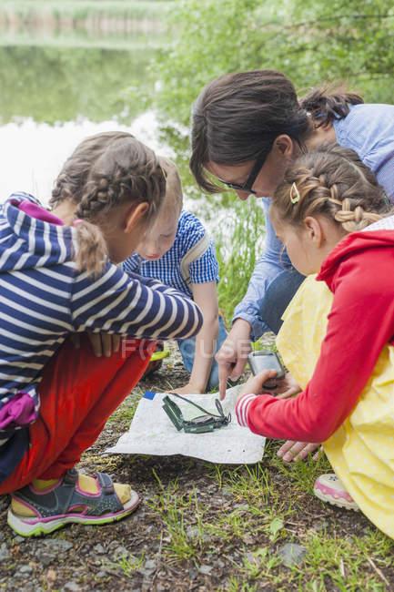 Les enfants apprennent à utiliser la boussole et la carte dans la nature — Photo de stock