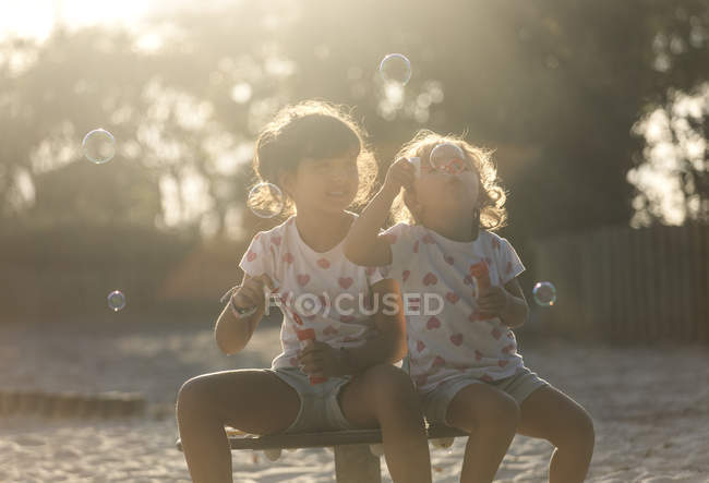 Two little sisters making soap bubbles in the park at twilight — Stock Photo