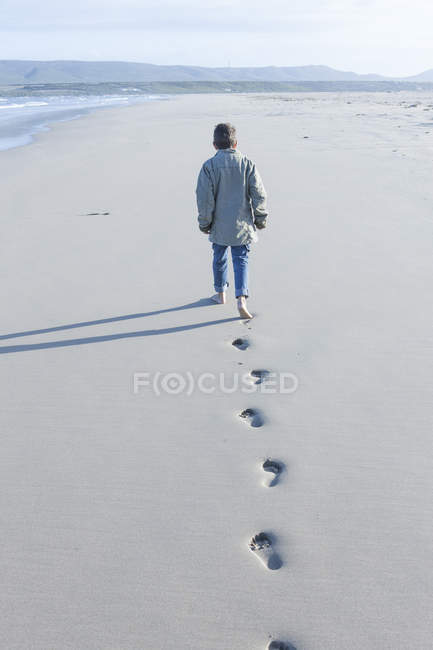 South Africa, Cape Town, back view of a boy walking on the beach — Stock Photo
