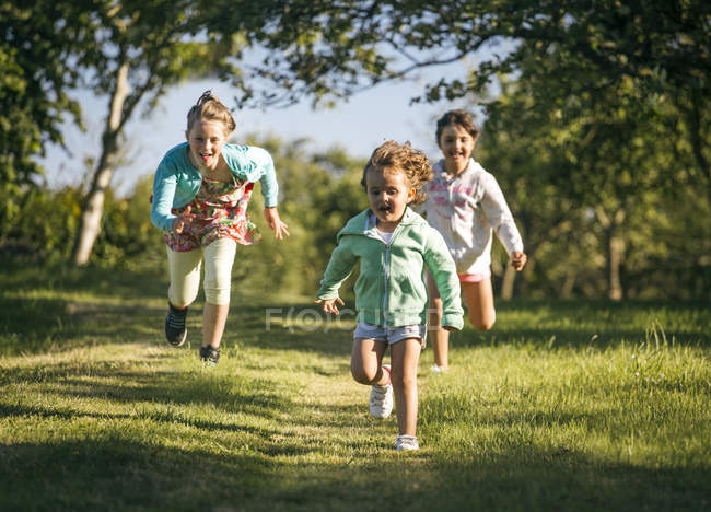 Three little girls running on green meadow in countryside — Stock Photo