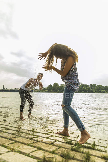 Playful young couple splashing with water by the riverside — Stock Photo