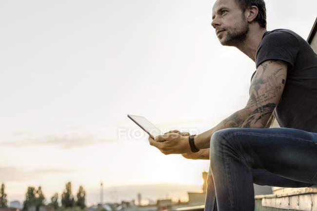 Німеччина, Берлін, зріла людина на даху тераса, використовуючи цифровий планшетний — стокове фото