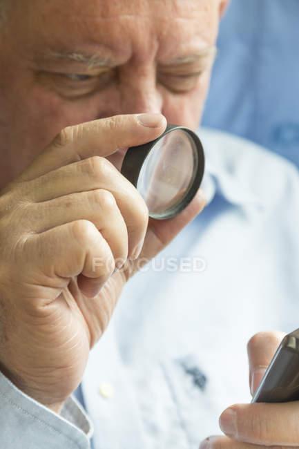 Старший читает текст на телефоне с увеличительным стеклом — стоковое фото