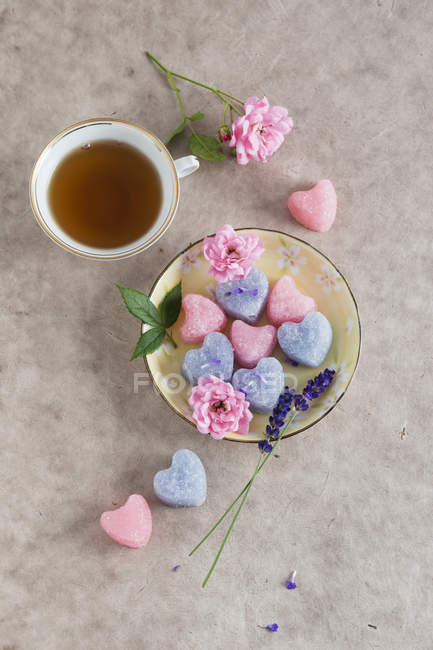 Cup of tea and sugar hearts with taste of roses or lavender — Stock Photo