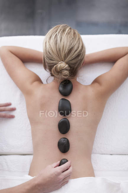 Mulher recebendo massagem de pedra quente em um spa — Fotografia de Stock