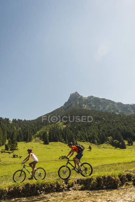 Austria, Tirol, Valle de Tannheim, pareja joven, montar en bici de montaña en riverside - foto de stock
