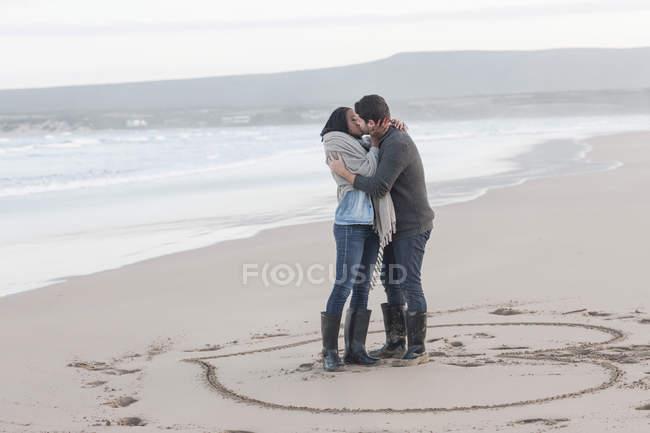 Молодая пара целуется на пляже — стоковое фото