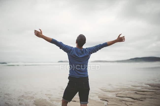 spain galicia ferrol man on the beach with outstretched arms