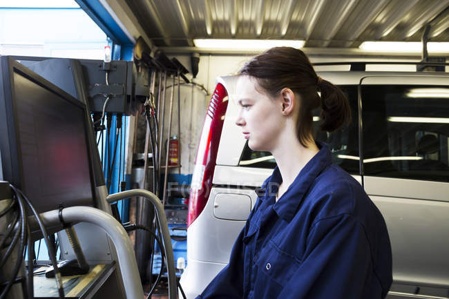 Young woman in repair garage checking car with electronic control — Stock Photo
