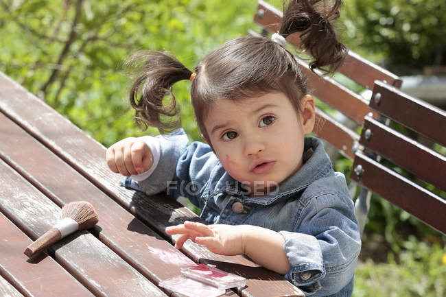 Portrait of little girl sitting at garden table with make-up brush and rouge — Stock Photo