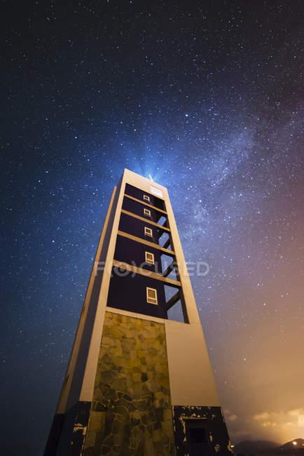 Spain, Valdovino, starry sky over lighthouse at night — Stock Photo