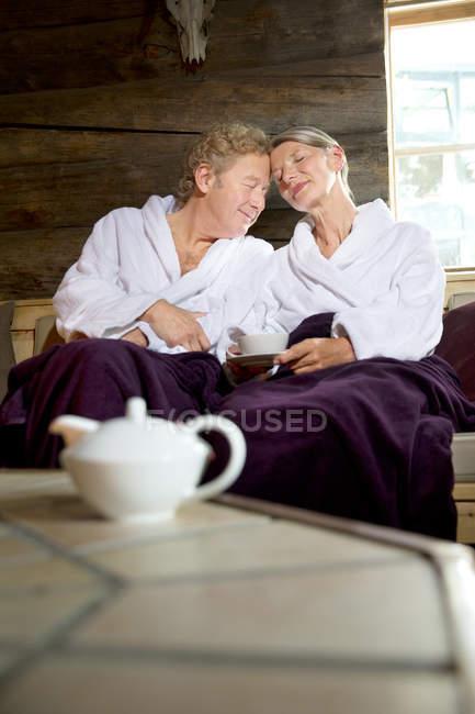 Couple sénior détendu assis sur un banc en peignoirs — Photo de stock