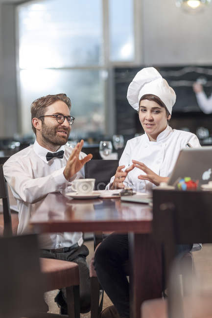 Restaurant chef and manager discussing menu — Stock Photo