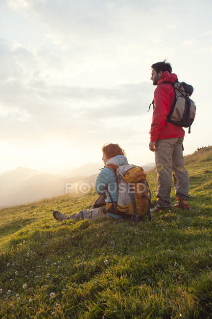 Austria, Tyrol, Unterberghorn, two hikers resting in alpine landscape at sunrise — Stock Photo