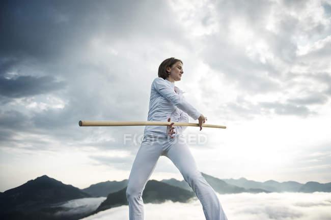 Österreich, Kranzhorn, Mitte erwachsene Frau übt mit Kampfstock auf Berggipfel — Stockfoto