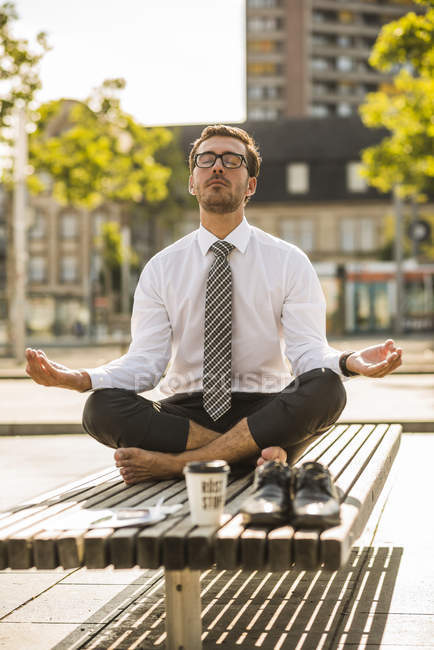 Young businessman meditating on bench — Stock Photo