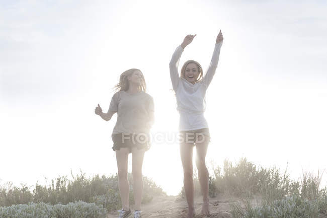 Two happy female friends on a beach dune at backlight at beautiful nature — Stock Photo