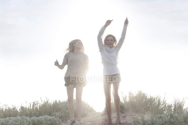 Duas amigas felizes em uma duna de praia no backlight na bela natureza — Fotografia de Stock