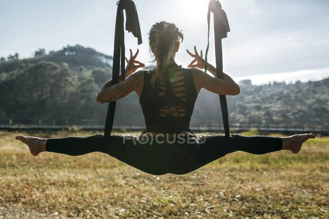 España, Villaviciosa, mujer practicando yoga aéreo al aire libre - foto de stock