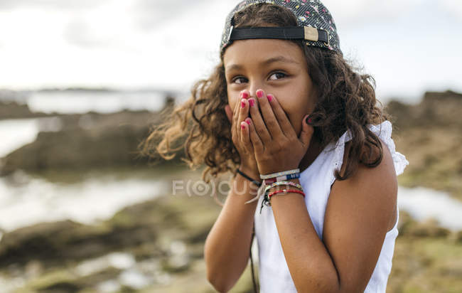 Portrait de petite fille couvrant la bouche avec ses mains — Photo de stock