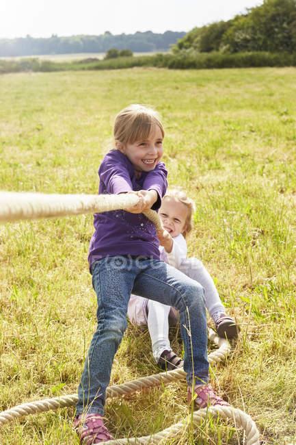 Дошкольника девочки, потянув веревку на лугу — стоковое фото