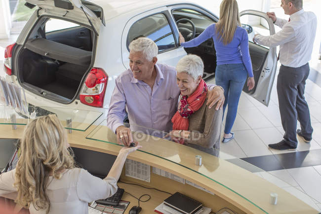 Clientes sênior no carro revendedor no showroom — Fotografia de Stock