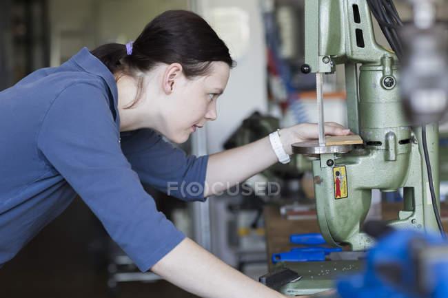 Mujer joven en taller trabajando con la máquina de aserrar - foto de stock