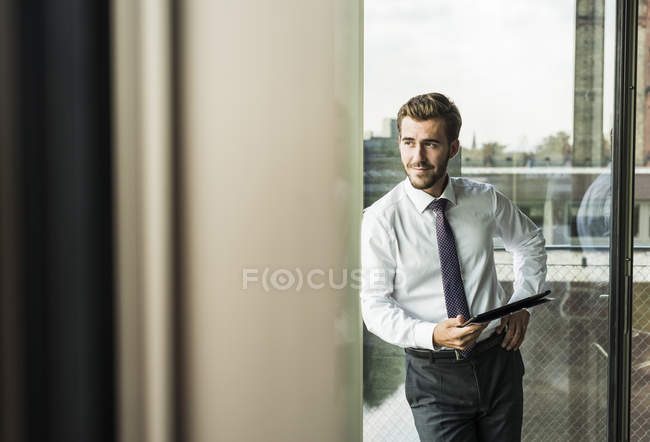 Smiling young businessman holding digital tablet — Stock Photo