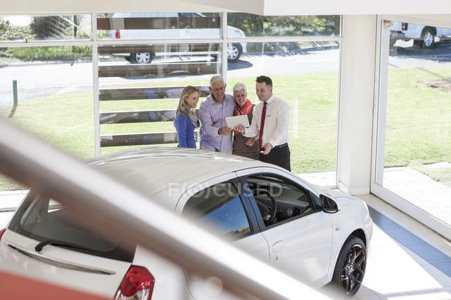 Customers at car dealer looking at digital tablet — Stock Photo
