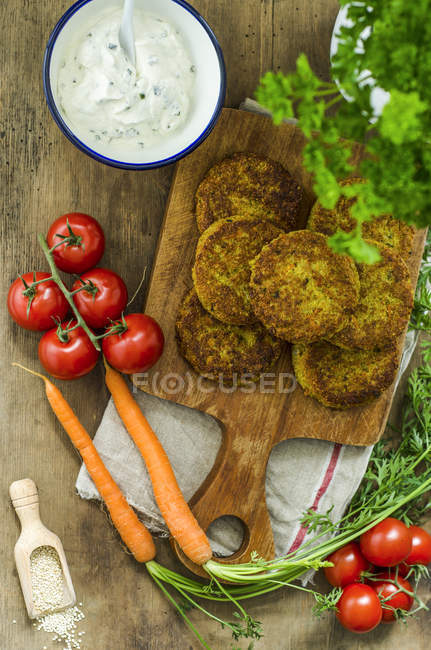 Quinoa fritters on wooden board and bowl of herb curd cheese — Stock Photo