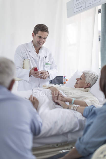 Family and doctor visiting patient in hospital — Stock Photo
