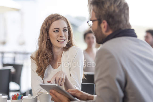 Couple using digital tablet at restaurant — Stock Photo