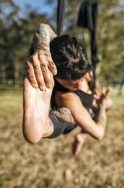 Spanien, villaviciosa, frau praktiziert luft-yoga im freien — Stockfoto