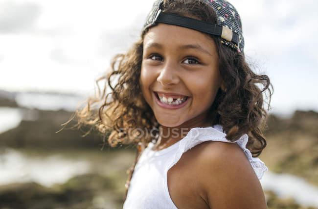 Portrait de petite fille souriante avec trou de dent sur la côte rocheuse — Photo de stock