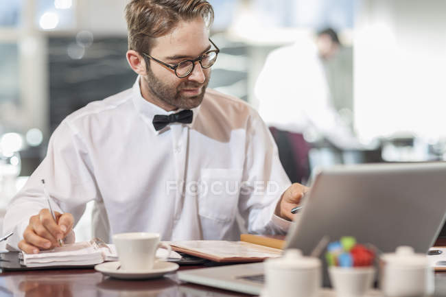 Restaurant employee sitting at table using laptop — Stock Photo