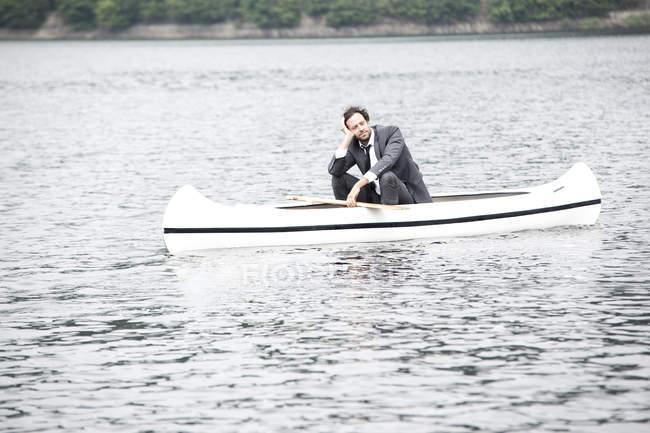 Homme d'affaires dans le costume de détente en canoë — Photo de stock