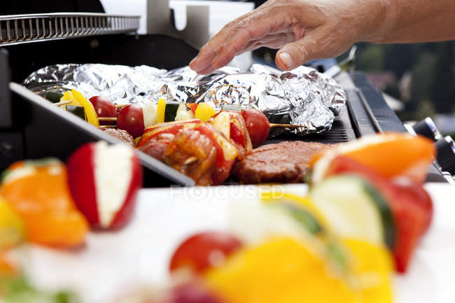 Vegetarian skewers and meat on barbecue grill — Stock Photo
