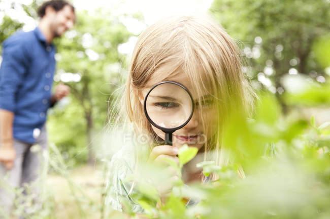 Девушка в природе смотрит через лупу — стоковое фото