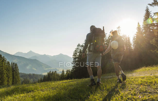 Austria, Tyrol, Tannheimer Tal, young couple hiking on alpine meadow in backlight — Stock Photo