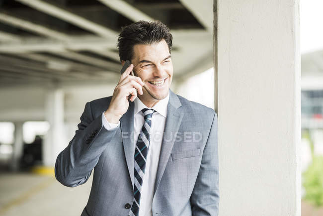 Portrait of smiling businessman telephoning with smartphone — Stock Photo